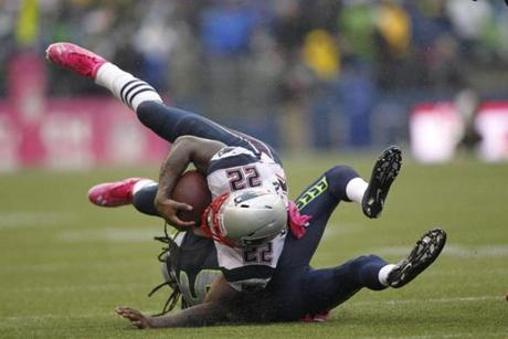 New England Patriots running back Stevan Ridley is upended by Richard Sherman in the second half.